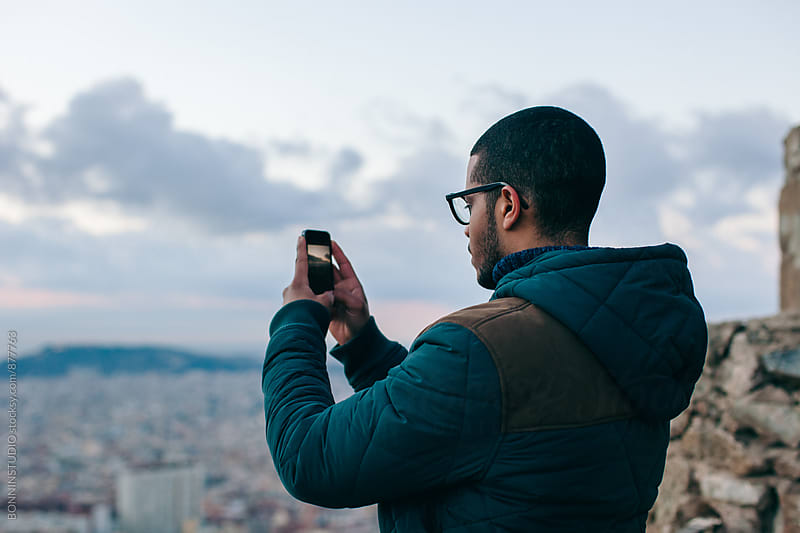 Man taking photo of Barcelona city using his smartphone. by BONNINSTUDIO for Stocksy United