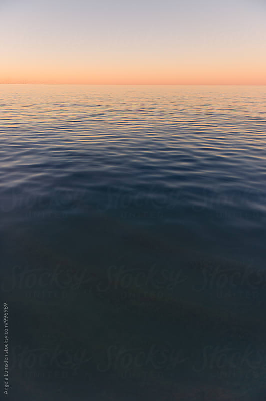 Calm water at the beach at sunset by Angela Lumsden for Stocksy United