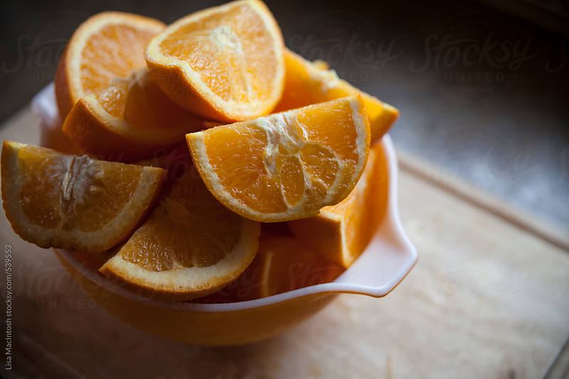 Oranges cut into quarters in vintage bowl by Lisa MacIntosh for Stocksy United