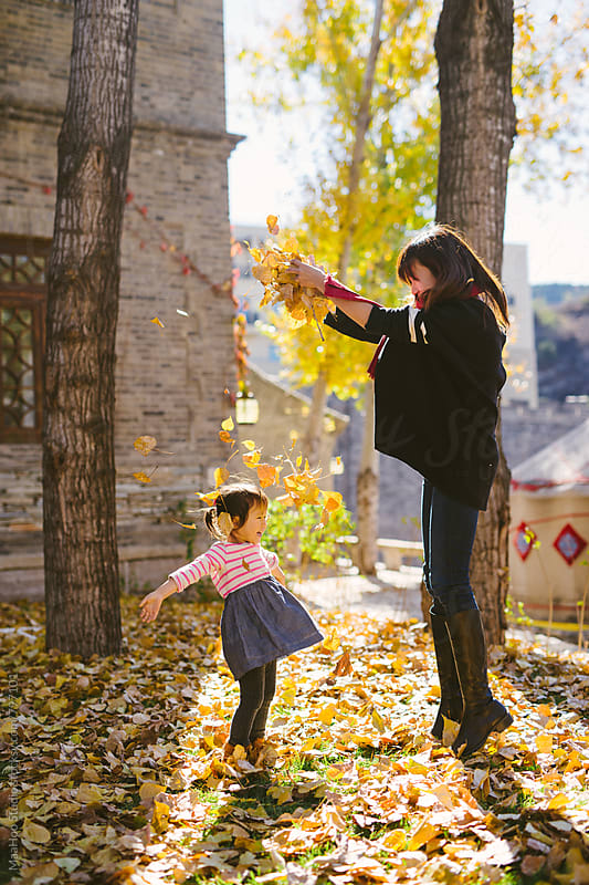 Young mother playing with her toddler daughter in autumn park by Maa Hoo for Stocksy United