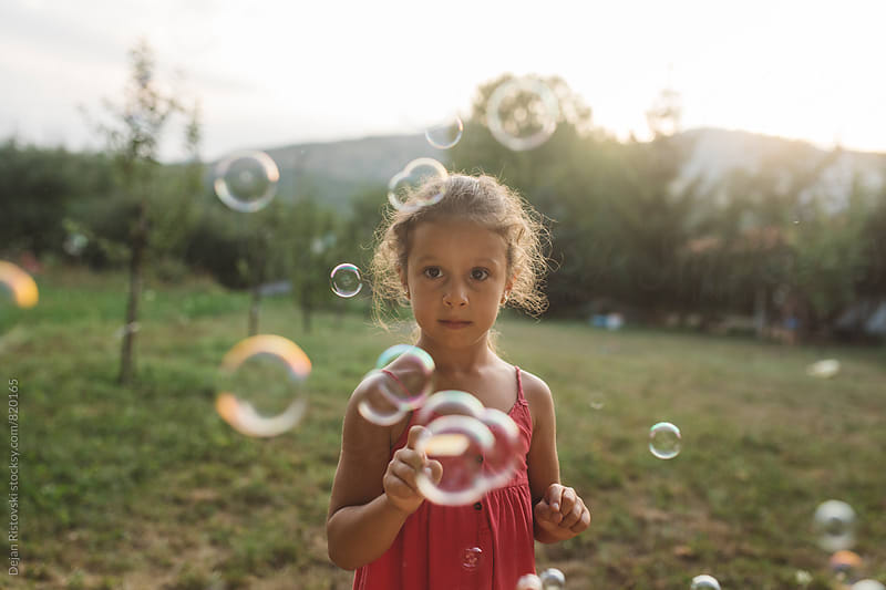 Little girl catching bubbles by Dejan Ristovski for Stocksy United