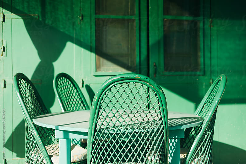 Green table and chairs by Sam Burton for Stocksy United