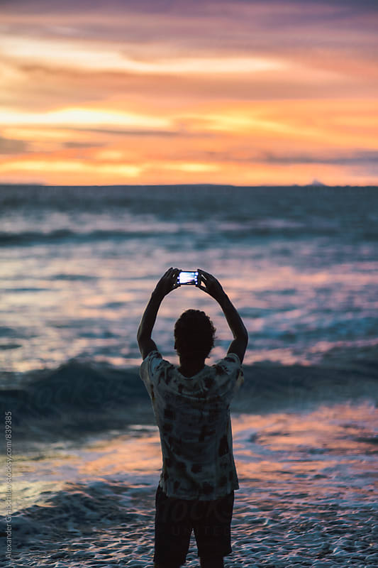 Man Taking A Photo Of A Sunset by Alexander Grabchilev for Stocksy United
