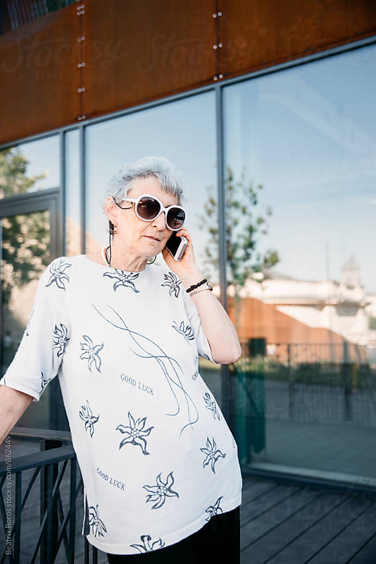 Senior woman talking on her cellphone outdoors in Spring time by Beatrix Boros for Stocksy United