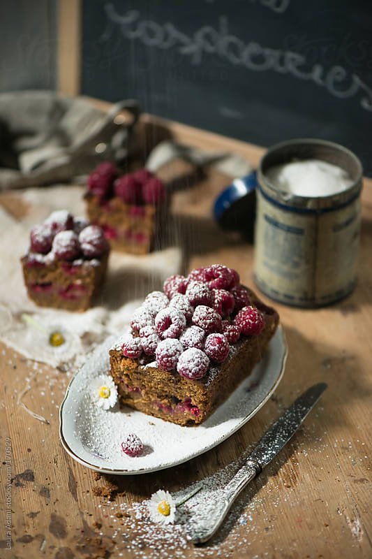 raspberries plum cake with a rain of iceing sugar by Laura Adani for Stocksy United
