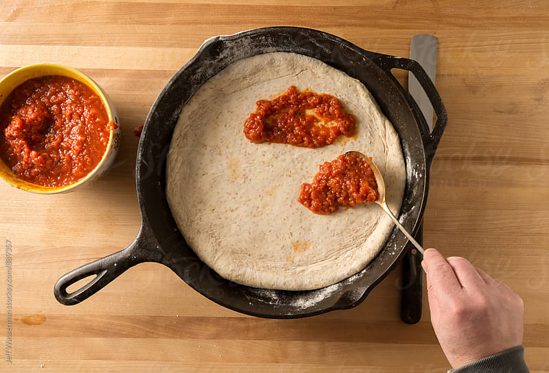 Putting Sauce on Dough for Skilet Pizza by Studio Six for Stocksy United