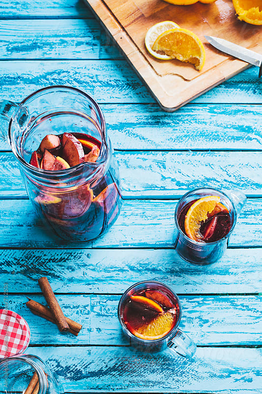 Orange, apple sangria on a blue wooden background by Aleksandar Novoselski for Stocksy United