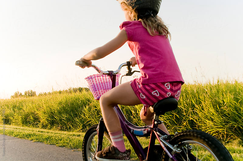 young girl on a bicycle  by Tomas Kraus for Stocksy United