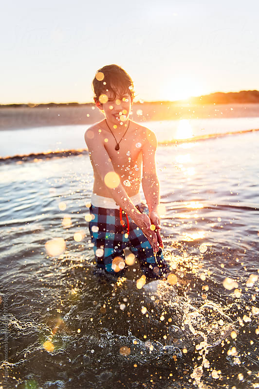 Child splashing water at the beach with the sun setting behind him by Angela Lumsden for Stocksy United