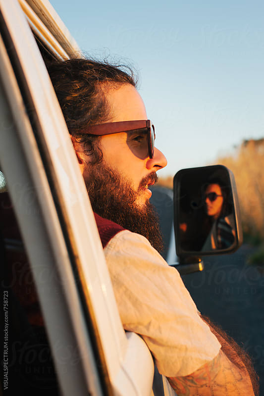 Bearded Male Hippie Looking Outside Car Window in Warm Sunset Light by VISUALSPECTRUM for Stocksy United