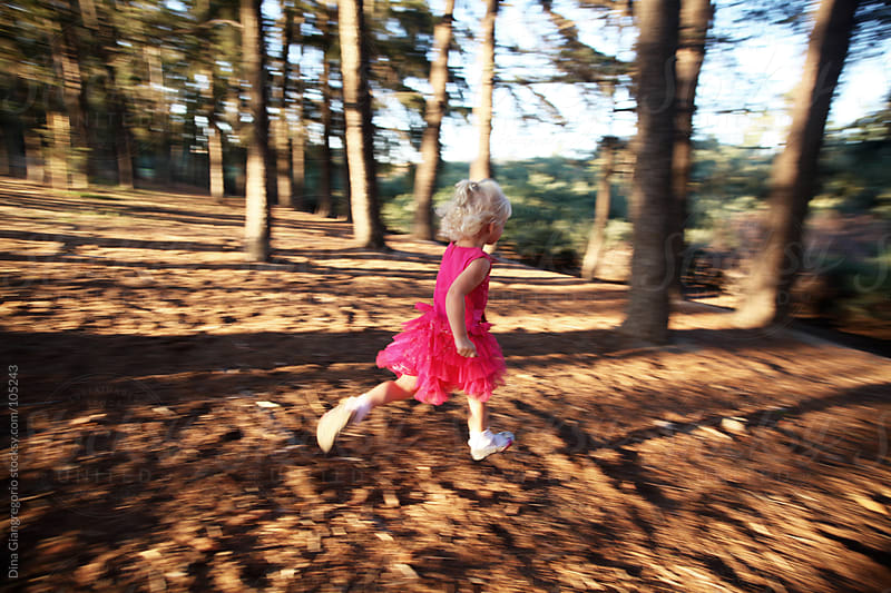 Blonde girl in pink dress running through a forrest  by Dina Giangregorio for Stocksy United