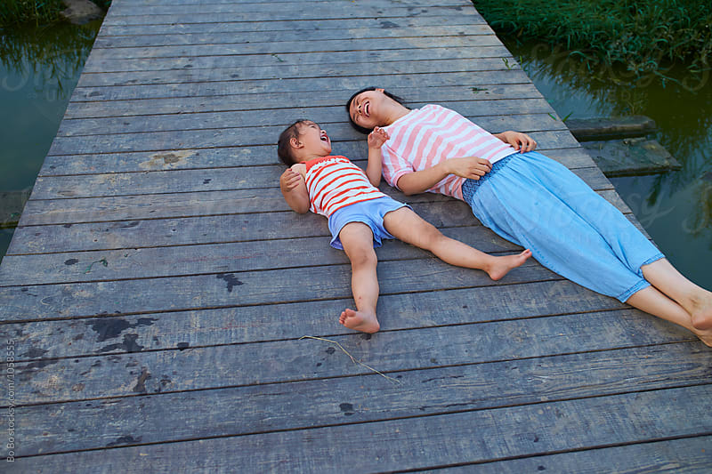little girl lying on the bridge with her mother by Bo Bo for Stocksy United