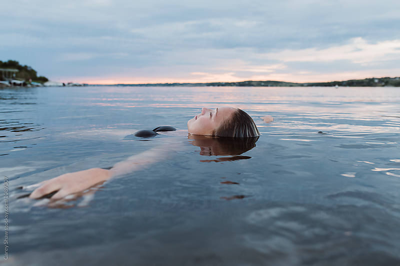 Woman floating in calm water at sunset by Carey Shaw for Stocksy United