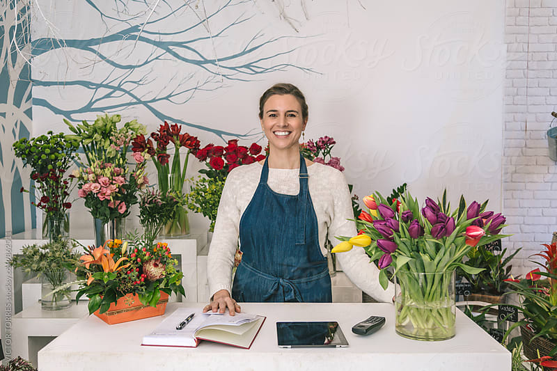Florist Working in a Small Flower Shop by VICTOR TORRES for Stocksy United
