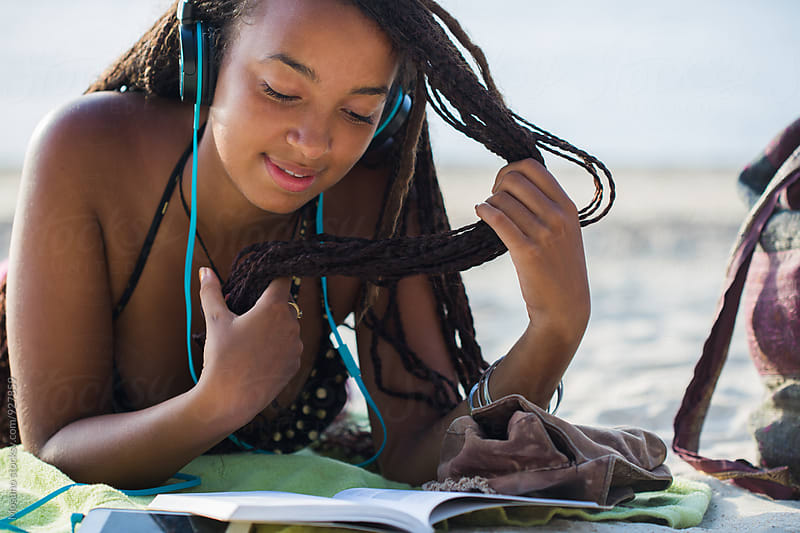 Young Black Woman Reading at the Beach by Mosuno for Stocksy United