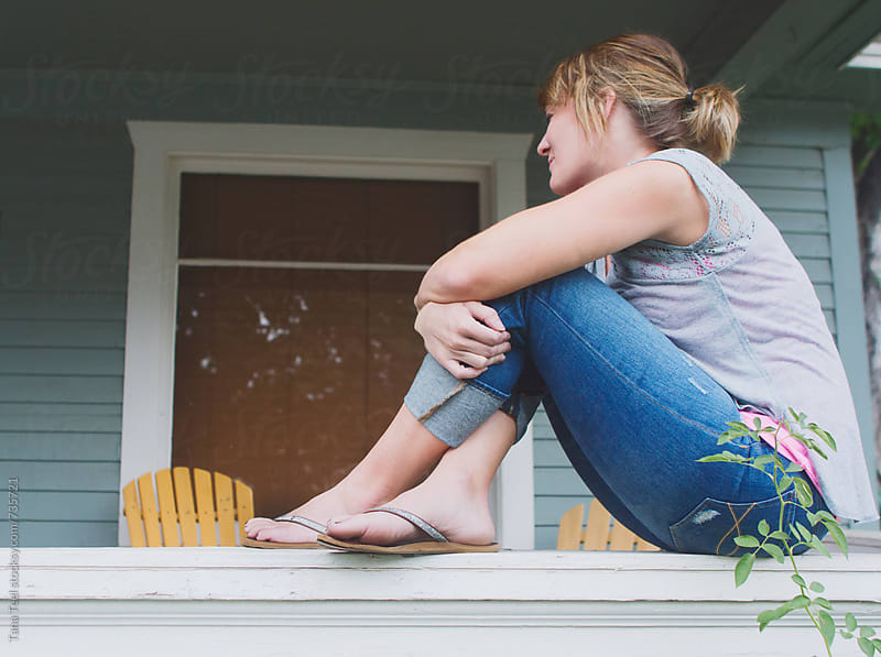 Woman sitting crossed leg on porch rail by Tana Teel for Stocksy United