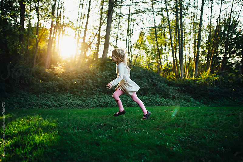 Little girl runs on the grass with the woods and setting sun behind her by Amanda Voelker for Stocksy United