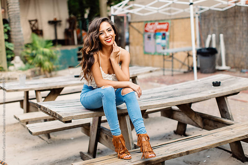 A beautiful woman sitting on a picnic table outdoors  by Kristen Curette Hines for Stocksy United