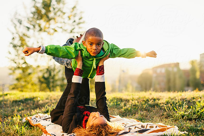 Mother and her son playing airplane in the park at sunset. by BONNINSTUDIO for Stocksy United