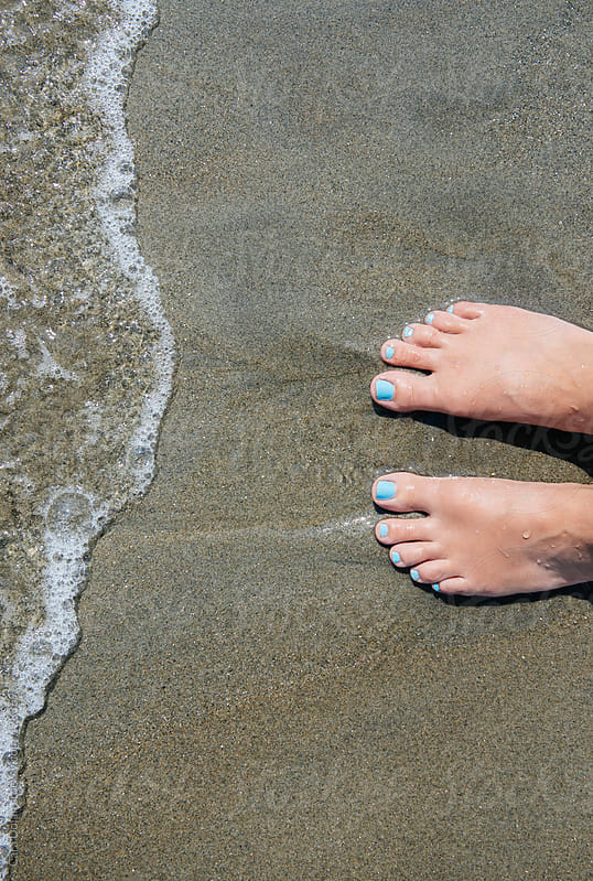 Woman's feet standing on a beach at the ocean's edge by Cara Dolan for Stocksy United