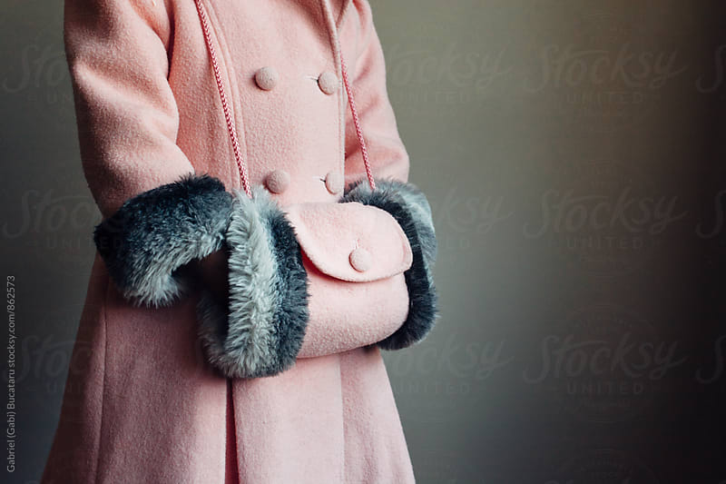 Little girl wearing a pink coat and hand muff by Gabriel (Gabi) Bucataru for Stocksy United
