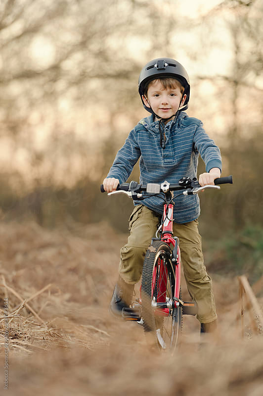 Cycling child in rural setting by Rebecca Spencer for Stocksy United
