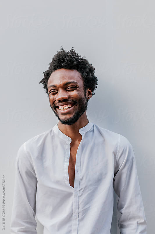 Afro American Man Smiling Over a White Wall by VICTOR TORRES for Stocksy United