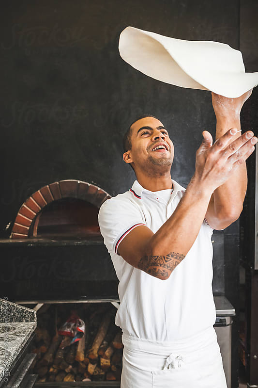 Adult Mixed Race Man Throwing the Pizza Dough by Giorgio Magini for Stocksy United