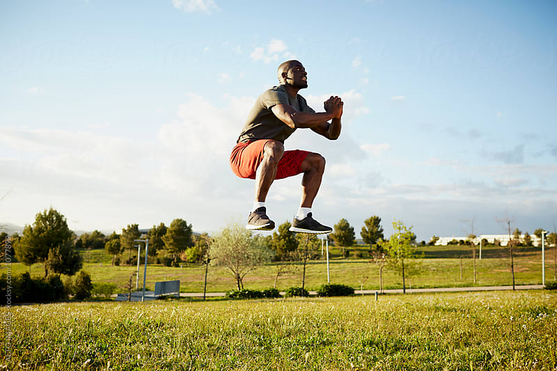Determined Male Athlete Jumping In Park by ALTO IMAGES for Stocksy United