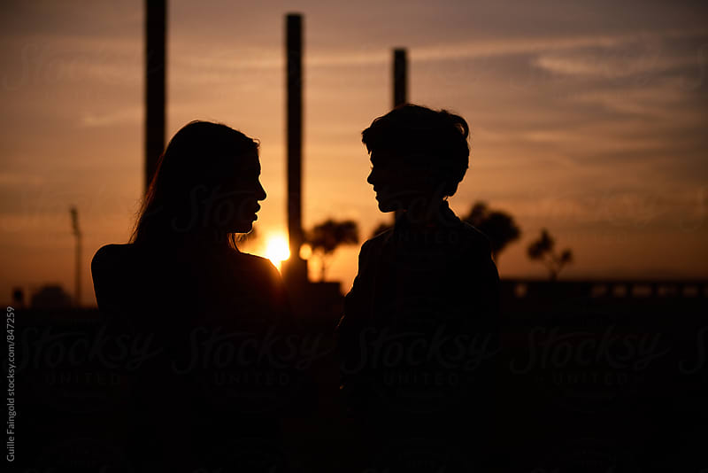 Silhouette of talking couple against of beautiful sunset by Guille Faingold for Stocksy United