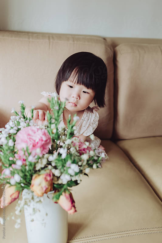 Asian baby girl with flower by Pansfun Images for Stocksy United
