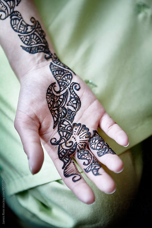 A hand with a painted henna tattoo by James Ross for Stocksy United