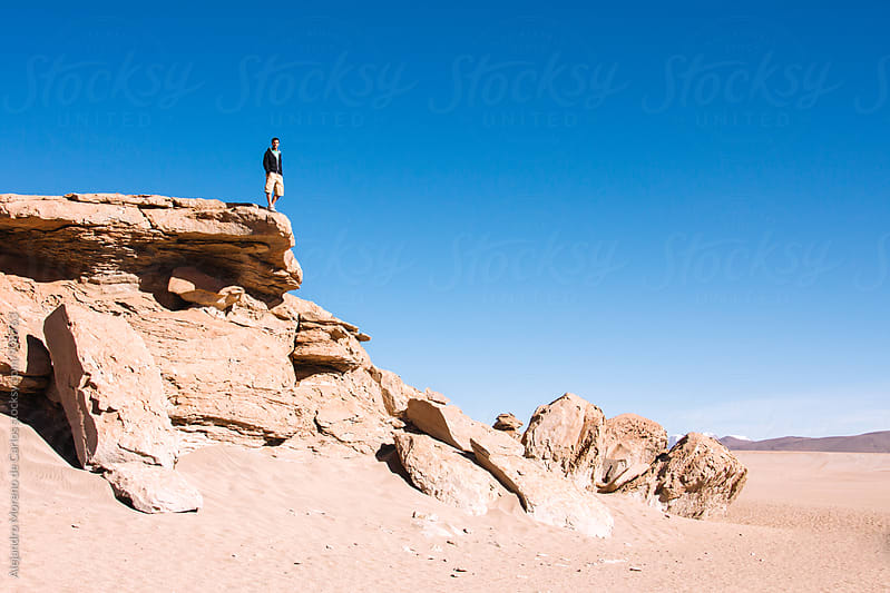 Man standing on stone edge against of blue sky by Alejandro Moreno de Carlos for Stocksy United
