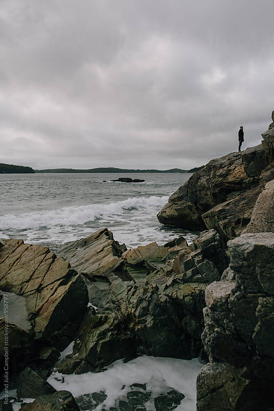Exploring man outside on rocks near ocean. by Rob and Julia Campbell for Stocksy United