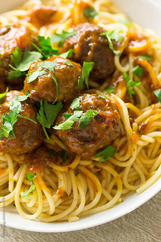 Beef meatballs on spaghetti with flat leaf parsley by Kirsty Begg for Stocksy United