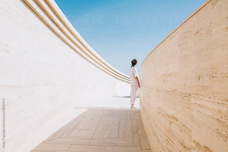 Woman in white standing in a passage by Maja Topcagic for Stocksy United