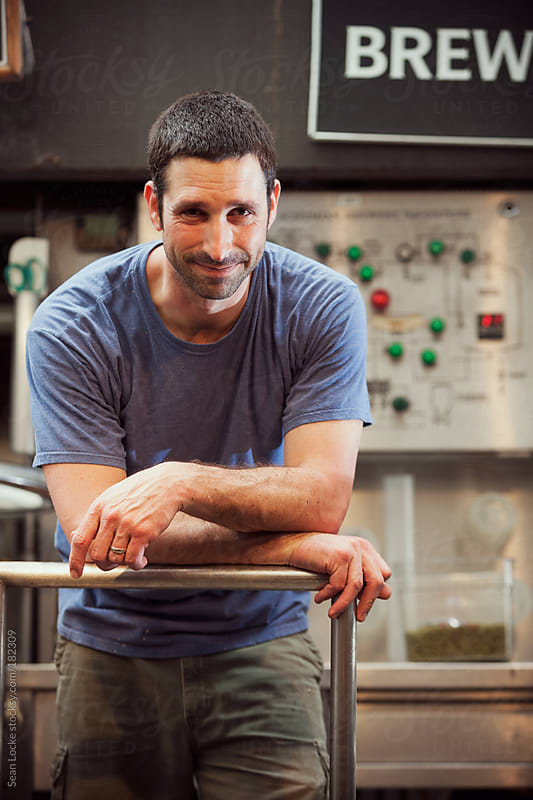 Beer: Smiling Brewer Leans And Looks To Camera by Sean Locke for Stocksy United