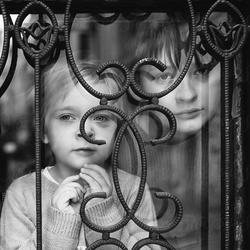 Two children look out of a window with ornate metal bars. by Julia Forsman for Stocksy United