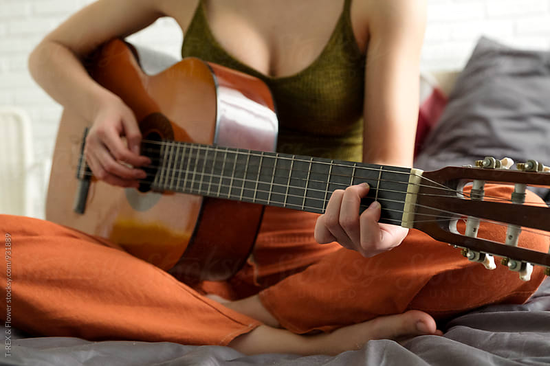 Close-up of woman playing guitar by Danil Nevsky for Stocksy United
