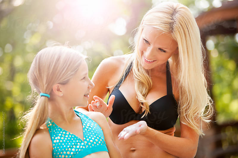 Swimming: Mother Applying Sunscreen To Child by Sean Locke for Stocksy United