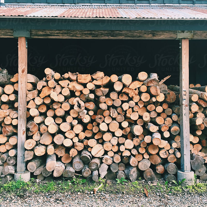 Logs Piled Up By A Building by Leslie Taylor for Stocksy United