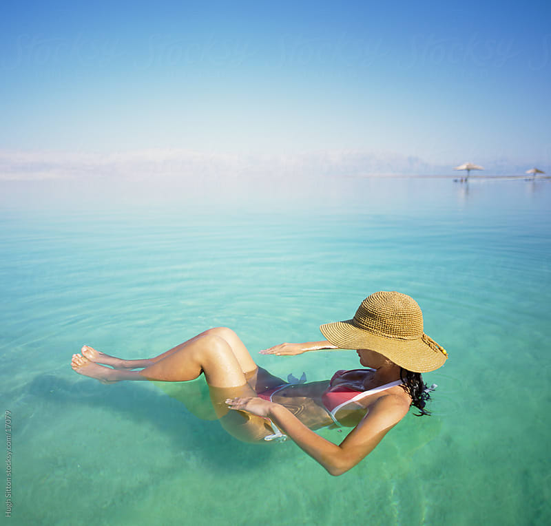 Woman floating on the Dead Sea. Israel by Hugh Sitton for Stocksy United