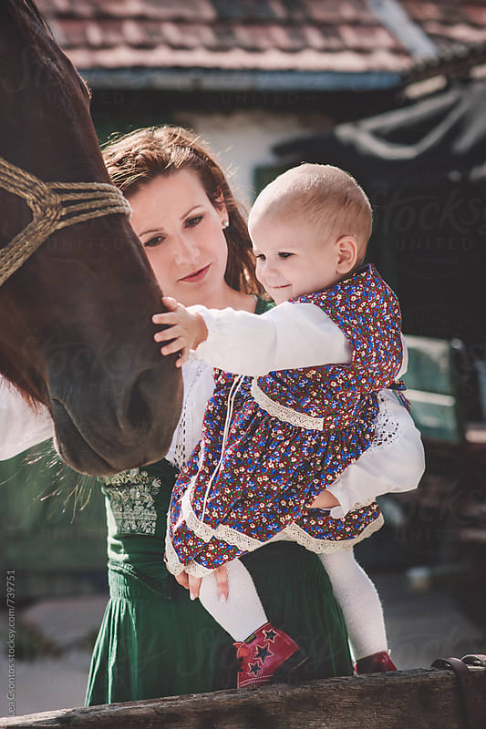 Mother and daughter stroking the head of a horse gently by Lea Csontos for Stocksy United
