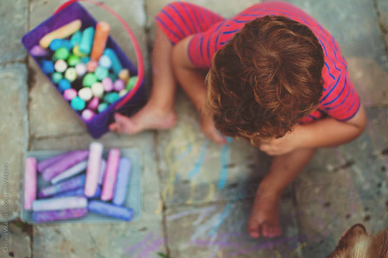 A young boy drawing with chalk. by Chelsea Victoria for Stocksy United