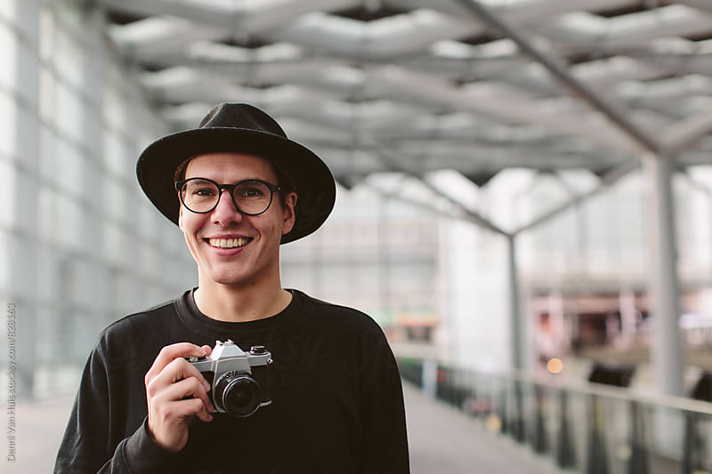 Portret of creative man holding analog camera  by Denni Van Huis for Stocksy United