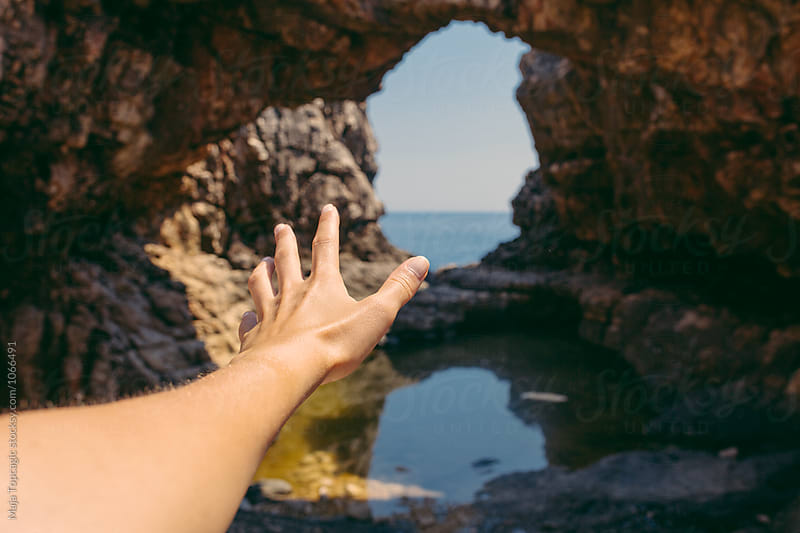 Female hand in front of a hidden cave  by Maja Topcagic for Stocksy United
