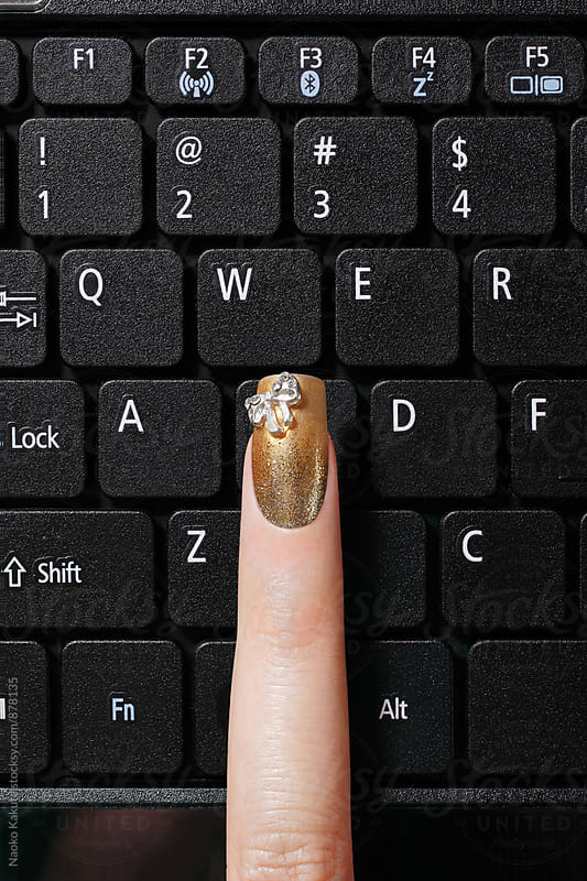 a finger with gold nail polish on black keyboard by Naoko Kakuta for Stocksy United