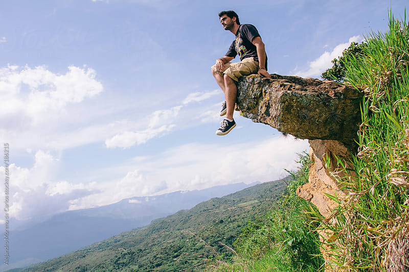 Adventurer man sitting on a rock with his feet dangling on natural landscape. Adventure travel by Alejandro Moreno de Carlos for Stocksy United