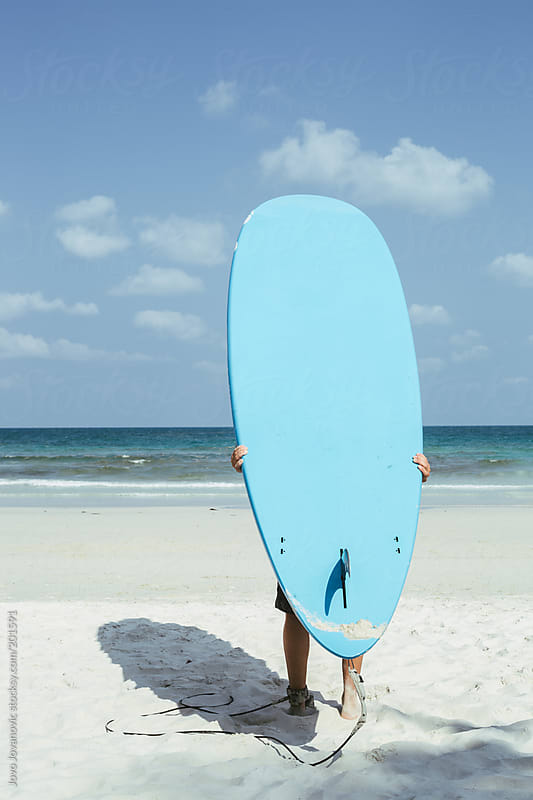 Man holding long surfing board on his back and watching at the waves by Jovo Jovanovic for Stocksy United