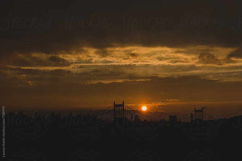 Sun setting over bridge and NYC by Lauren Naefe for Stocksy United